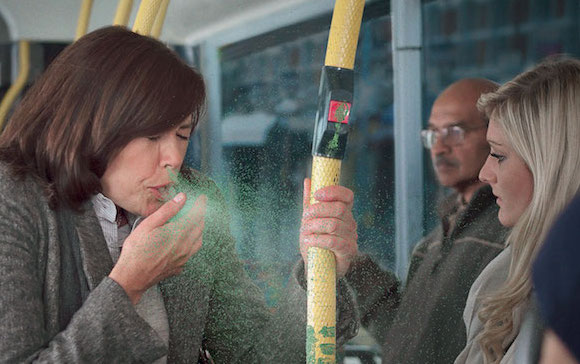 A woman sneezing on a bus.